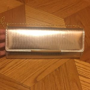 Also gold clutch with gold chain